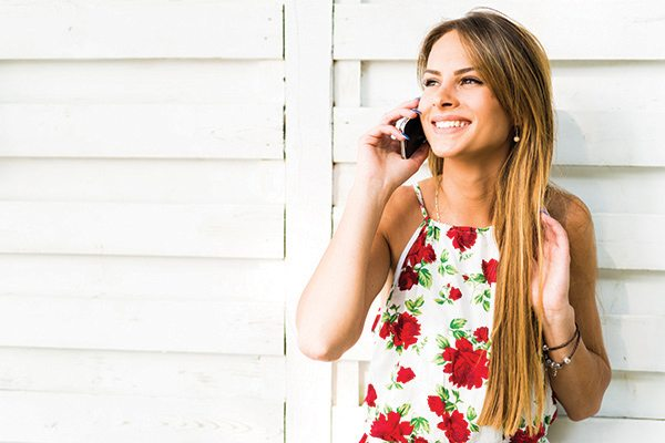 Beautiful young happy woman smiling during a phone call while leaning against a white wall