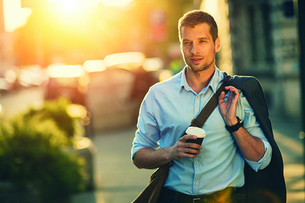 Photo of a handsome man having takeaway coffee in city_73383545