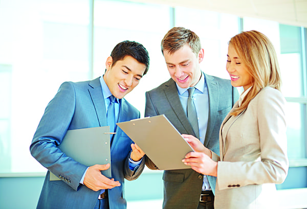 Smiling business partners reading a document on clipboard